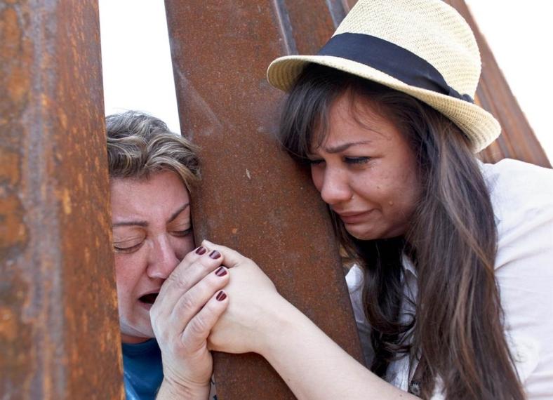 Renata Teodoro, de 25 años, a la derecha, sostiene la mano de su madre, Gorete Borges Teodoro, quien fue deportada hace seis años de los Estados Unidos, a través de la valla fronteriza en Nogales, Arizona.